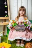Little girl with a basket of flowers in her hands Royalty Free Stock Photo