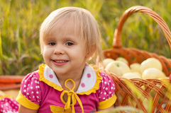 Little girl with basket of fresh apples Royalty Free Stock Photo