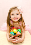 Little girl with basket full of colorful easter eggs Stock Photos