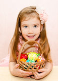 Little girl with basket full of colorful easter eggs Stock Images