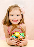 Little girl with basket full of colorful easter eggs Stock Image