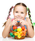 Little girl with basket full of colorful eggs Stock Photography