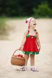 Little girl with basket full of strawberries Stock Image