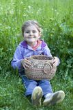 Little girl with basket on grass Stock Images