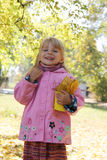 Little girl with basket and leaves in autumn park Stock Image