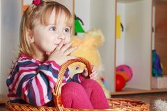 Little girl with basket playing Stock Images