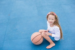 Little girl with basketball on the outdoor court Stock Images