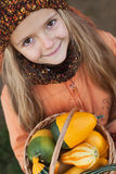Little girl with a basketful of pumpkins Royalty Free Stock Photography