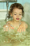 A little girl bathes. Stock Photos