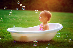 Little girl bathes in a bath with soap bubbles.  Royalty Free Stock Images