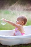 Little girl bathes in a bath with soap bubbles.  Stock Image