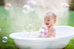 Little girl bathes in a bath with soap bubbles Stock Photos
