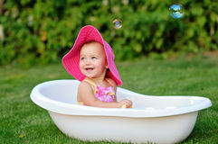 Little girl bathes in a bath with soap bubbles Royalty Free Stock Photography