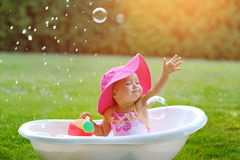 Little girl bathes in a bath with soap bubbles Stock Images