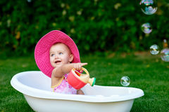 Little girl bathes in a bath with soap bubbles stock photo