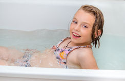 Little girl bathes in a bathroom. Royalty Free Stock Photos