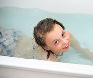 Little girl bathes in a bathroom. Stock Photos