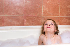 Little girl bathes in bathtub with foam Stock Photos
