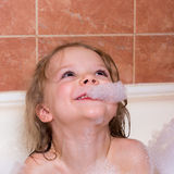 Little girl bathes in bathtub with foam Stock Photography