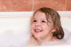 Little girl bathes in bathtub with foam Stock Images