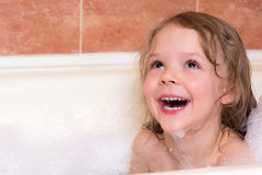 Little girl bathes in bathtub with foam Royalty Free Stock Photos