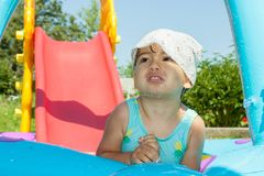 Little girl bathes in pool. In the garden Stock Photography
