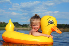 Little girl bathes in river in inflatable duck Stock Photos