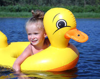 Little girl bathes in river in inflatable duck. Little girl bathes in summer river in inflatable duck royalty free stock image