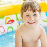 Little girl bathes in yellow Inflatable Swimming Paddling Pool o Royalty Free Stock Images