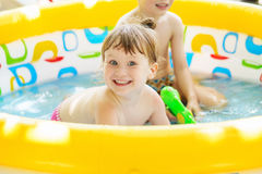 Little girl bathes in yellow Inflatable Swimming Paddling Pool o Royalty Free Stock Image
