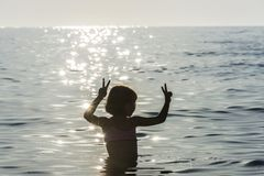 Little girl bathing in the sea doing the victory sign. Surrounded by sunbeam reflections in summer in Sicily, Italy stock photo