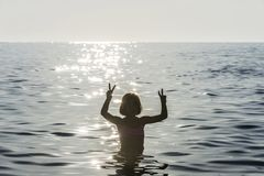 Little girl bathing in the sea doing the victory sign. Surrounded by sunbeam reflections in summer in Sicily, Italy royalty free stock images