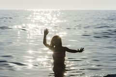 Little girl bathing in the sea surrounded by sunbeam reflections. Little girl bathing and dancing in the sea surrounded by sunbeam reflections in summer in stock images