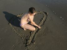 Little girl with bathing suit draws a big heart on the wet sand. Of the sea Stock Images