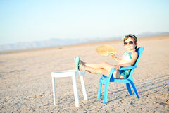 Little Girl In Bathing Suit With Fan In Hot Desert. Little girl in vintage style bathing suit sitting on a chair fanning herself in the middle of the desert Stock Image