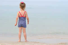 Little girl in a bathing suit looking at sea, rear view, space f. Or text. Charming baby standing on the seashore, summer photo Royalty Free Stock Photos