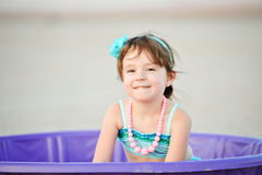 Little Girl In bathing Suit in Plastic Pool. Little girl in vintage style bathing suit in a purple plastic pool in the middle of the desert Royalty Free Stock Photography
