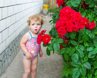The little girl in a bathing suit is in the yard and with astonishment looks aside. Near her the big beautiful flower grows Stock Photography