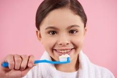 Little girl in bathrobe is brushing teeth stock images