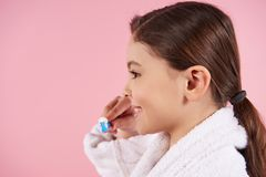 Little girl in bathrobe is brushing teeth royalty free stock photography