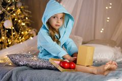 Little girl in bathrobe. Christmas. Little girl in a bathrobe is sitting on the bed. Christmas tree with ornaments in the background. Happy childhood royalty free stock photos