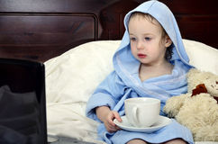 Little girl in a bathrobe relaxing on the bed Stock Images