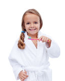 Little girl in bathrobe washing teeth Stock Image