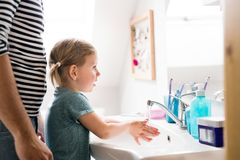 Little girl in bathroom with father washing hands. Cute little girl at home in bathroom with her father washing hands Stock Photos