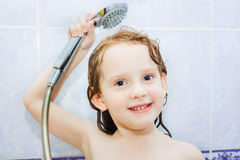 Little girl in the bathroom holding a shower Stock Photography
