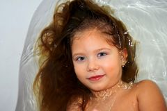 The little girl in the bathroom under running water, beautiful drops the person royalty free stock photo