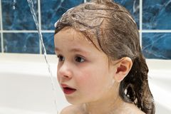 Little girl in bathroom washing her hair. The symbol of purity a. Nd hygiene education Stock Photo