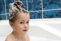 Little girl in bathroom washing her hair. The symbol of purity a. Nd hygiene education Stock Photography