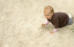 Little girl on a beach. Baby girl playing in the sand. With plenty of copy space Stock Photos