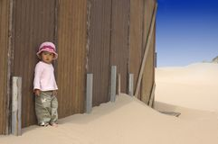 Little girl at the beach. Sweet little girl leaning against a beachhouse Royalty Free Stock Image